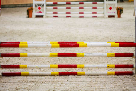 equitation: Equitation. Yellow red white obstacle for jumping horses. Riding competition. Real.