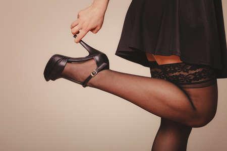 sexualidad: La belleza, la sexualidad y la seducción. Mujer parte del cuerpo sexy con un vestido negro y medias de las bragas con tacones altos. estudio de disparo.