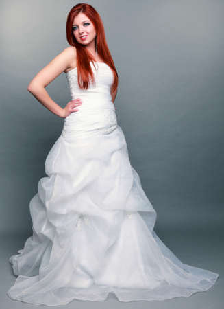 grey eyed: Wedding day. Portrait of happy beautiful blue eyed red haired bride long white dress in full length studio shot on gray background Stock Photo