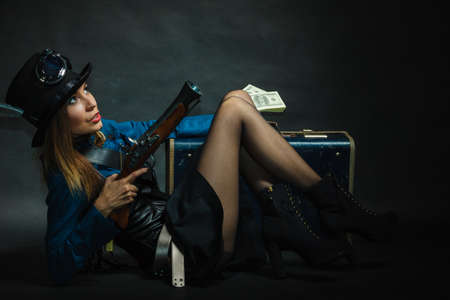 flintlock: Fashionable subculture weapon concept. Steampunk girl with cash. Young gorgeous lady in victorian fashion lying on floor with banknotes briefcase and blunderbuss. Stock Photo