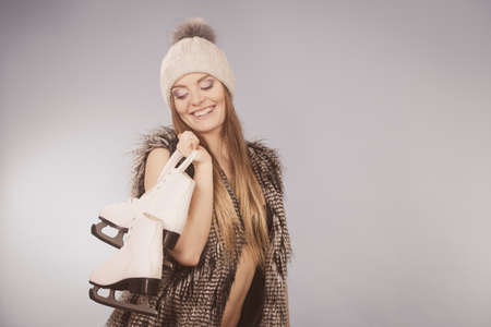 brassiere: Winter, sport, people concept. Smiling lady with pair of skates. Young woman is wearing fur and white cap. Stock Photo