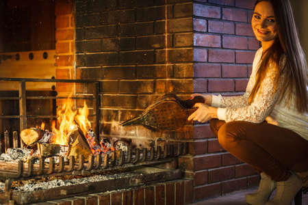 fireplace bellows: Woman at fireplace making fire with bellows. Young girl heating warming up and relaxing. Winter at home. Stock Photo