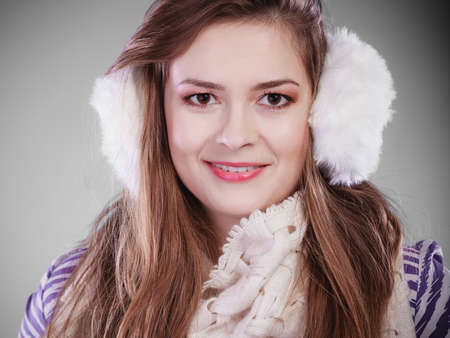Smiling teenage girl wearing fluffy white earmuff in winter fashion, cold time.