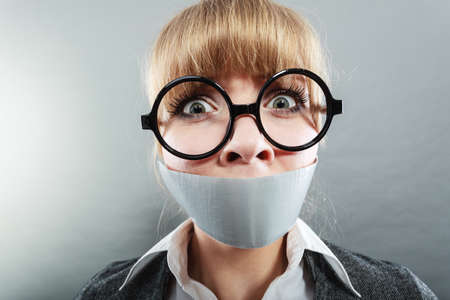 censorship: Scared woman with mouth taped shut. Afraid young girl with duct tape on lips. Censorship and freedom of speech concept.