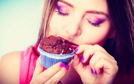 indulging: Sweet food sugar make us happy. Smiling woman holds cake chocolate muffin in hand blue background