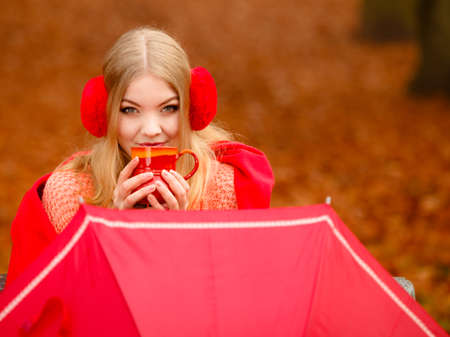 Happiness carefree and fall concept. Young happy woman relaxing in the autumn park on bench enjoying hot drink holding red mug with warm beverage. Orange leaves background Stock Photo