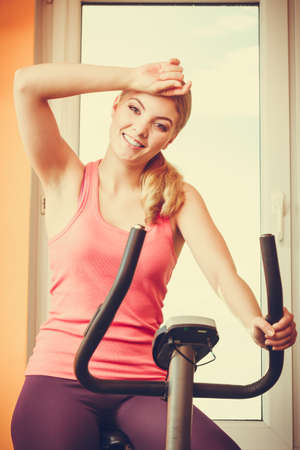 stationary bicycle: Active young woman working out on exercise bike stationary bicycle. Sporty girl training at home. Fitness and weight loss concept.