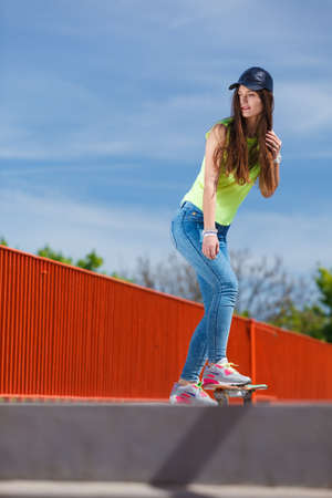Summer sport and active lifestyle. Cool teenage girl skater riding skateboard on the street. Outdoor.