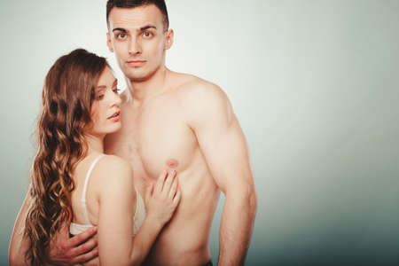 half nude: Sexy passionate young couple lovers embracing in studio. Handsome muscled half naked semi nude man and pretty gorgeous woman in lingerie. Love and passion.