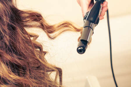 Stylist curling hair for young woman. Girl care about her hairstyle Stock Photo