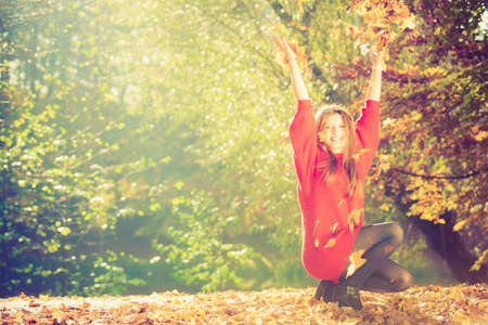crouching: Crouching girl in autumnal forest.  Young woman playing with leaves. Nature relax outdoor leisure concept.