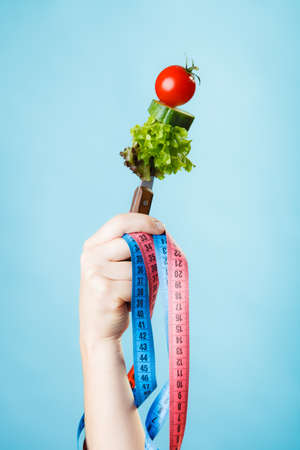 dietician: Diet and weight loss concept. Dietician woman hand with vegetarian food and colorful measuring tapes on blue background.