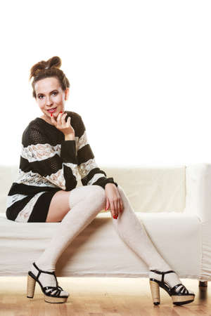 hosiery: Fashion young woman in full length. Girl in fashionable striped dress high heels posing on white couch.