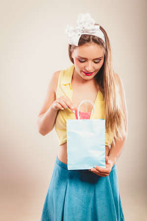 paperbag: Retro pin up girl shopping. Woman dive into paperbag. Stock Photo