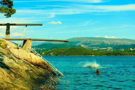 springboard: Las vacaciones de verano y el deporte peligroso. Vista de trampolín. Trampolín para bucear en el agua. Fiordo paisaje