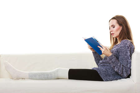living wisdom: Leisure, education, literature and home concept. Woman sitting on couch reading book at home