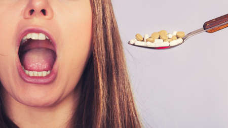 swallowing: Closeup of woman patient taking pills blindly without thinking. Girl female eating stack of tablets. Drug addict and health care concept. Overdose.