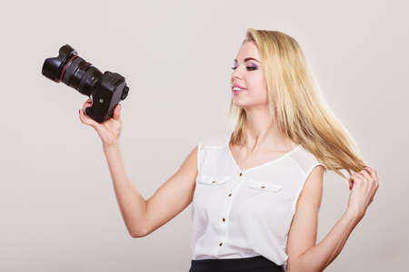 Photographer girl shooting images. Lovely blonde woman with professional camera on gray background