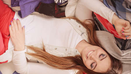 messy room: Happy woman in messy room on stack of clothes. Disorder and mess at home. Stock Photo