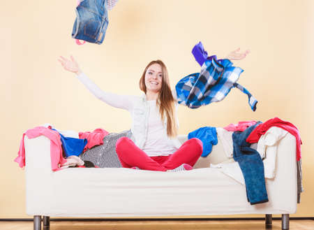 messy clothes: Happy woman sitting on sofa couch in messy living room throwing clothes. Young girl surrounded by many stack of clothing. Disorder and mess at home.