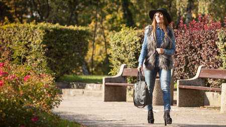 Female fashion. Attractive long haired model wearing stylish clothes walking in park. Fashionable young model spending time on air.