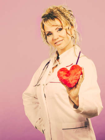 the cardiologist: Help people concept. Medical idea of helping. Mature blonde happy doctor cardiologist with red heart enjoy her work. Middle aged woman wearing medic apron. Filtered. Stock Photo