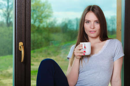 mornings: People mornings concept. Beautiful woman drinking morning coffee. Attractive young lady chilling out. Stock Photo