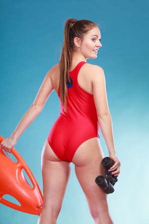Lifeguard with rescue tube buoy and binoculars. Woman supervising swimming pool water. Accident prevention and rescue. Stock Photo