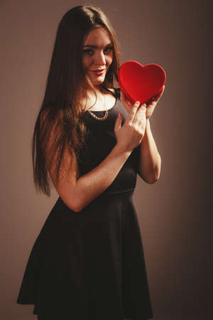 Love help and charity concept. Young beauty cute happy long haired woman girl in black dress holding heart box gift present in studio.