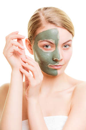 Skin care. Woman in clay mud mask on face isolated on white. Girl taking care of dry complexion. Beauty treatment. Stock Photo