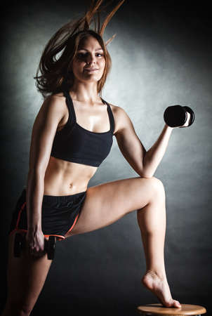 dumb bells: Fitness girl fit woman lifting dumbbells weights doing exercise with dumb bells training shoulder muscles motion wind blowing hair gray background