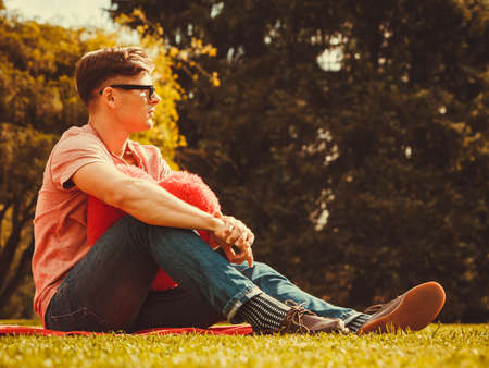 heartbreak: Love romance sadness heartbreak concept. Young man resting in park. Sad boy sitting with heart. Stock Photo