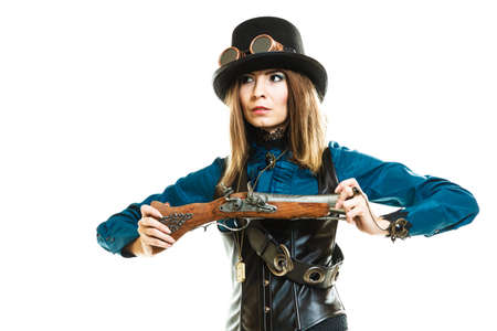 subculture: Young steampunk islolated girl on white holding fancy rifle. Fantasy old fashion wearing hat and goggle. Stock Photo