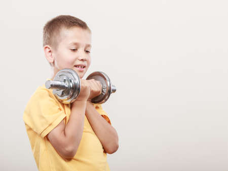 care about the health: Sports boy making exercise with heavy dumbbell. Care about health and body