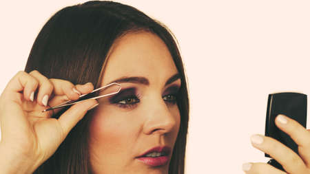 plucking: Make up and cosmetics. Woman plucking eyebrows depilating with tweezers. Attractive girl tweezing eyebrows looking at mirror Stock Photo