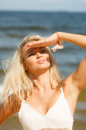 covering eyes: Pretty young blonde pretty girl at beach covering eyes. Woman have active time in summer. Summertime carefree concept. Stock Photo
