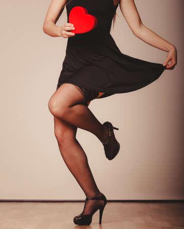 sexualidad: La belleza, la sexualidad y la seducci�n. Mujer atractiva con la parte del cuerpo rect�ngulo rojo del coraz�n presentes bailando regalo en el estudio. Foto de archivo