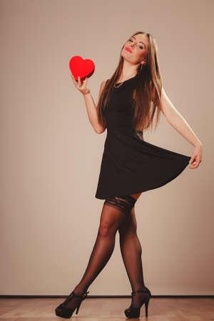 sexualidad: La belleza, la sexualidad y la seducci�n. Joven atractivo modelo atractivo de la mujer de longitud completa con caja de regalo presente coraz�n rojo bailando en el estudio.