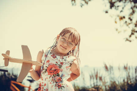 Little girl child kid having fun with cardboard paper plane airplane outdoor. Summer vacation holiday relax and fun.