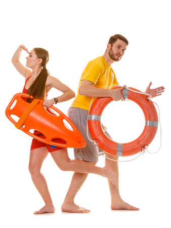 Lifeguards running with rescue tube and ring buoy on duty. Man and woman supervising swimming pool. Accident prevention. Stock Photo