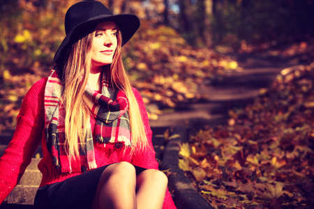 checkered scarf: Outdoors fashion autumn season concept. Attractive lady sitting on sidewalk. Woman wearing black stylish hat, red sweather and checkered scarf.