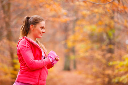 Healthy lifestyle concept. Portrait of attractive sporty smiling girl wearing sports clothes. Woman prepare herself to exercising in autumnal forest. Stock Photo