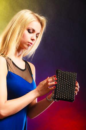 clutch bag: Fashion elegant evening outfit. Stylish woman fashionable blonde girl holding black rivet leather handbag bag in night club dancing.