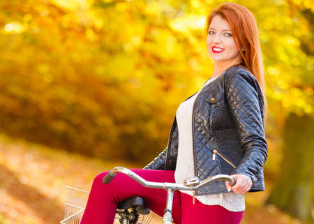 Cycling nature outdoor relax and fashion concept. Fashionable girl with bike. Redhead well dressed lady taking walk through autumnal park leading bicycle.