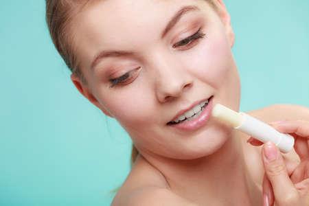 chap sticks: Female putting applying lip balm moisturizing balsam. Girl taking care of lips. Skincare. Stock Photo