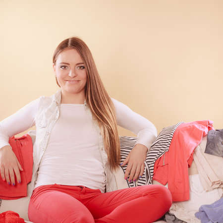 messy clothes: Happy woman sitting on sofa couch in messy room. Girl surrounded by stack of clothes. Disorder and mess at home.