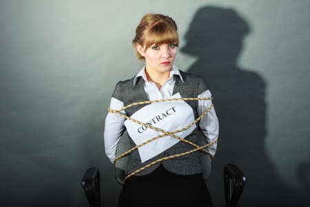 helpless: Upset businesswoman bound by contract terms and conditions.  Helpless woman tied to chair become slave. Business and law concept.