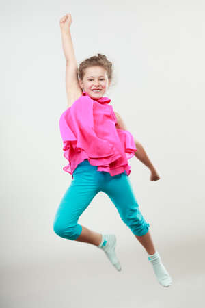 Excited happy little girl jumping for joy in air. Joyful cheerful kid in studio with arm raised up.