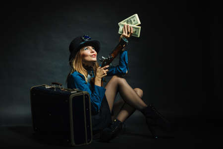 subculture: Fashionable subculture weapon concept. Steampunk girl with cash. Young gorgeous lady in victorian fashion lying on floor with banknotes briefcase and blunderbuss. Stock Photo