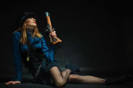 flintlock: Subculture fashionable victorian elegant weapon concept. Steampunk girl armed and dangerous. Lady dressed in victorian fashion holding antique firearm aiming. Stock Photo